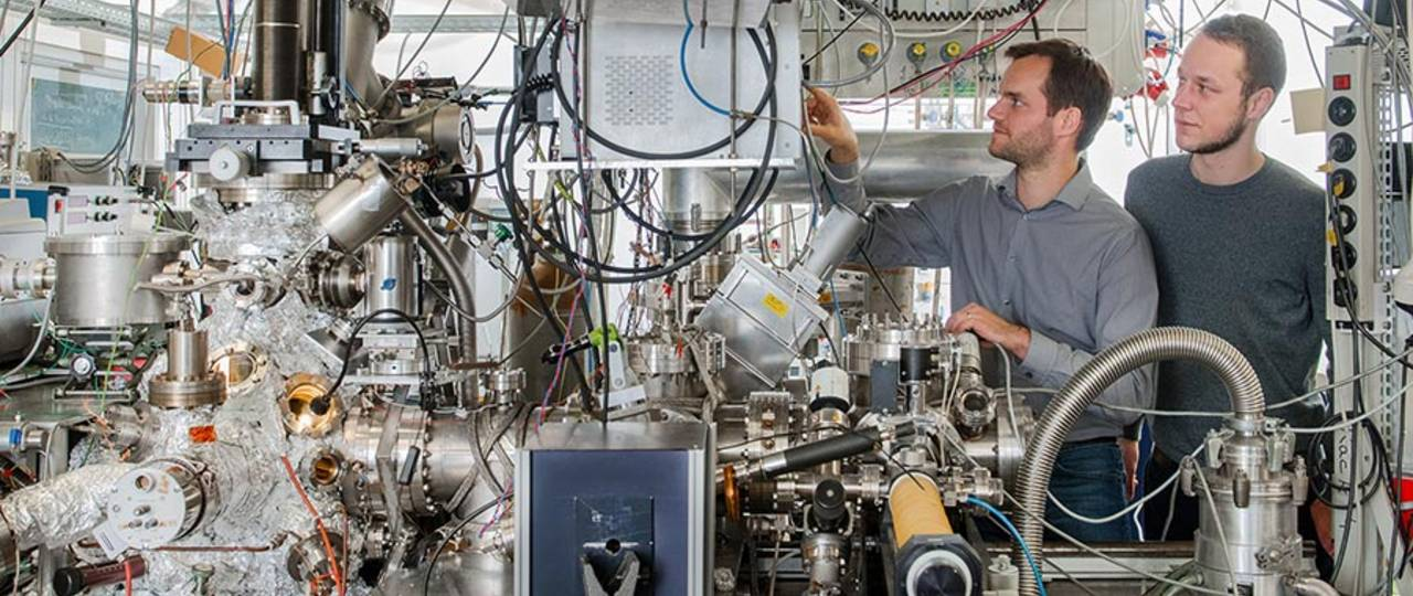 Andrew Crampton and Marian Rötzer at their vacuum chamber for production of ultra-small catalyst particles - Photo: Andreas Heddergott / TUM