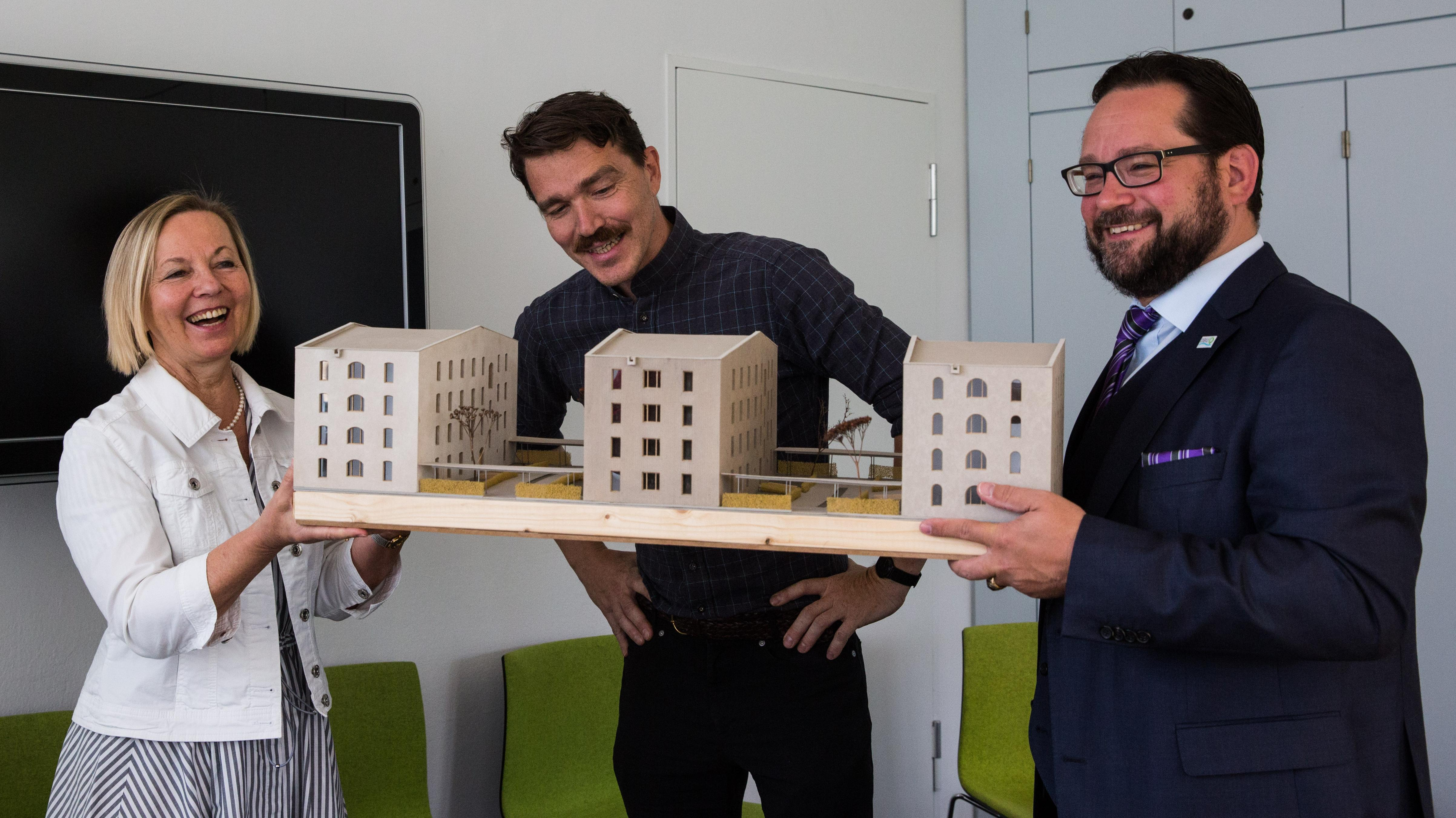 Dr. Ursula Wurzer-Faßnacht, architect Tilmann Jarmer and Alexander Bonde (from left to right) with a model of the houses in Garching.