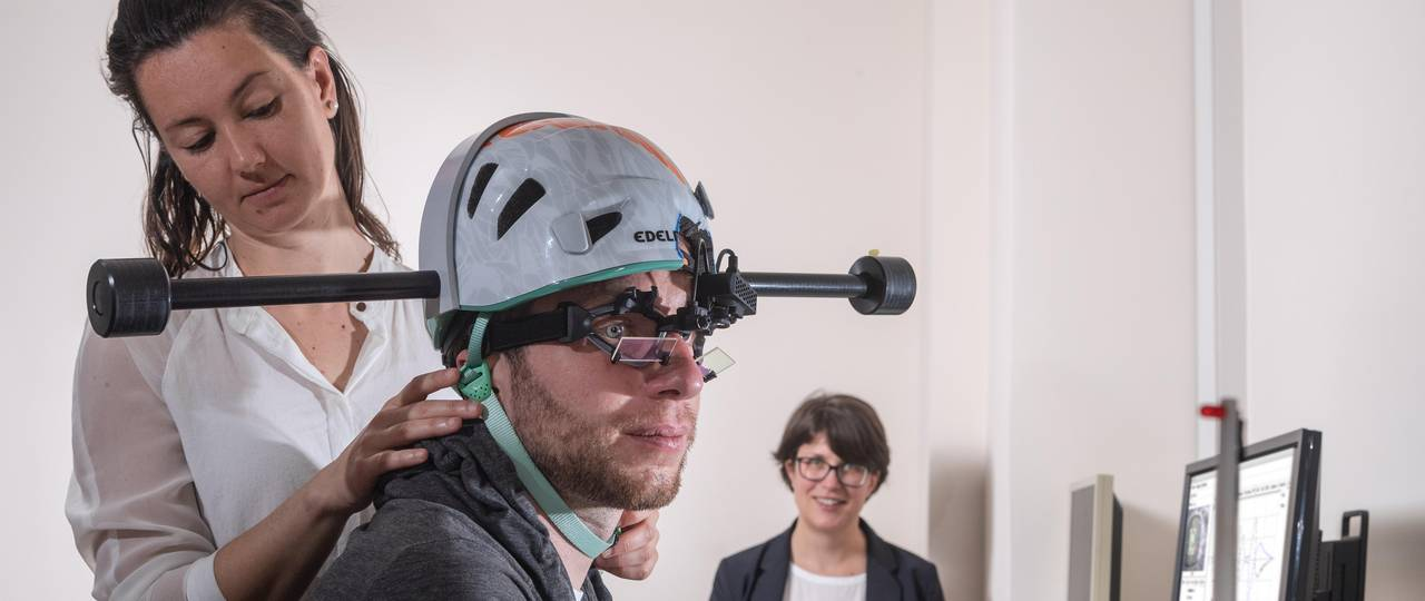 Dr. Cecilia Ramaioli (left) checks if the weighted helmet fits correctly to the head of a study participant. In the background, Prof. Nadine Lehnen prepares the computer for the experiment.