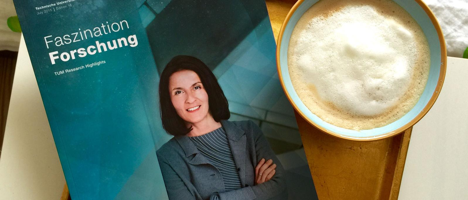 "Cover of ""Faszination Forschung"" next to a coffee cup"