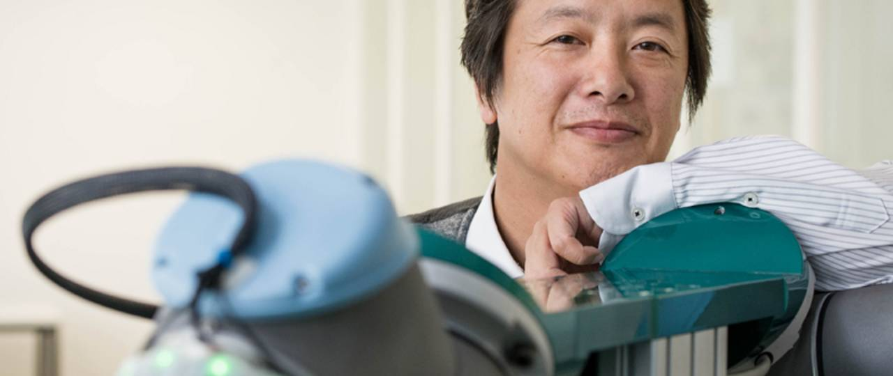 TUM Prof. Gordon Cheng standing next to one of his robotic creations: A robotic arm sheathed in the artificial skin developed by Gordon and his team.