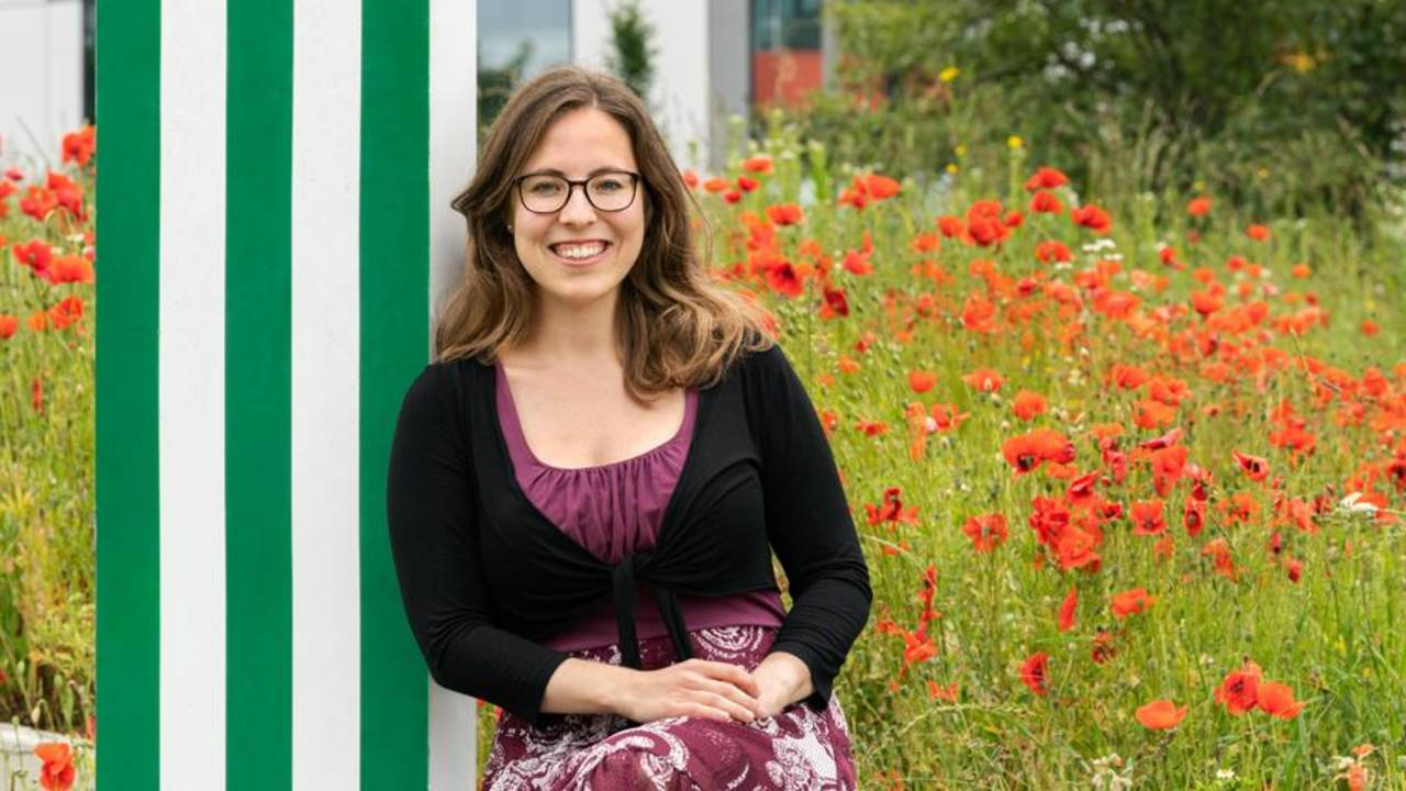 Michaela Wilfling in front of a field with poppies