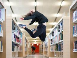 Woman jumping in front of bookshelf
