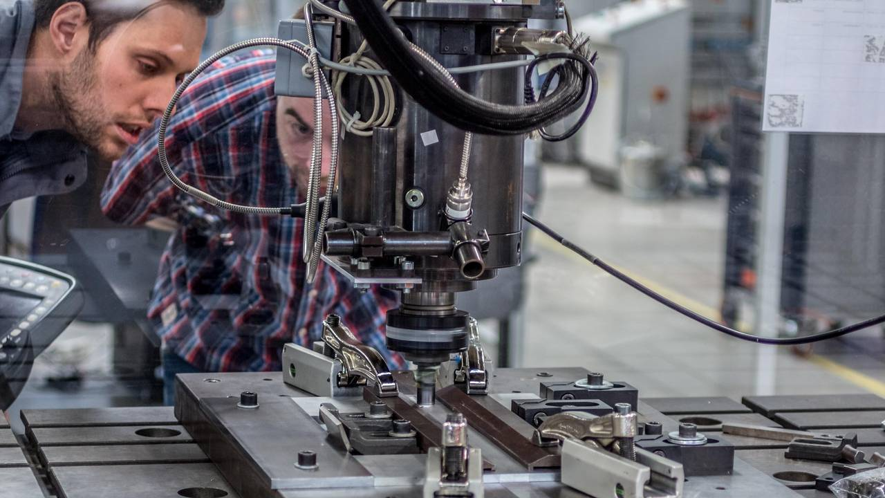 Dr. Andreas Bachmann (left) watches through a safety glass as the robot welds two metal plates together with the rapidly rotating welding pin.