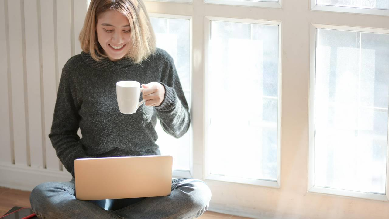 Woman with laptop and coffee cup in her apartment