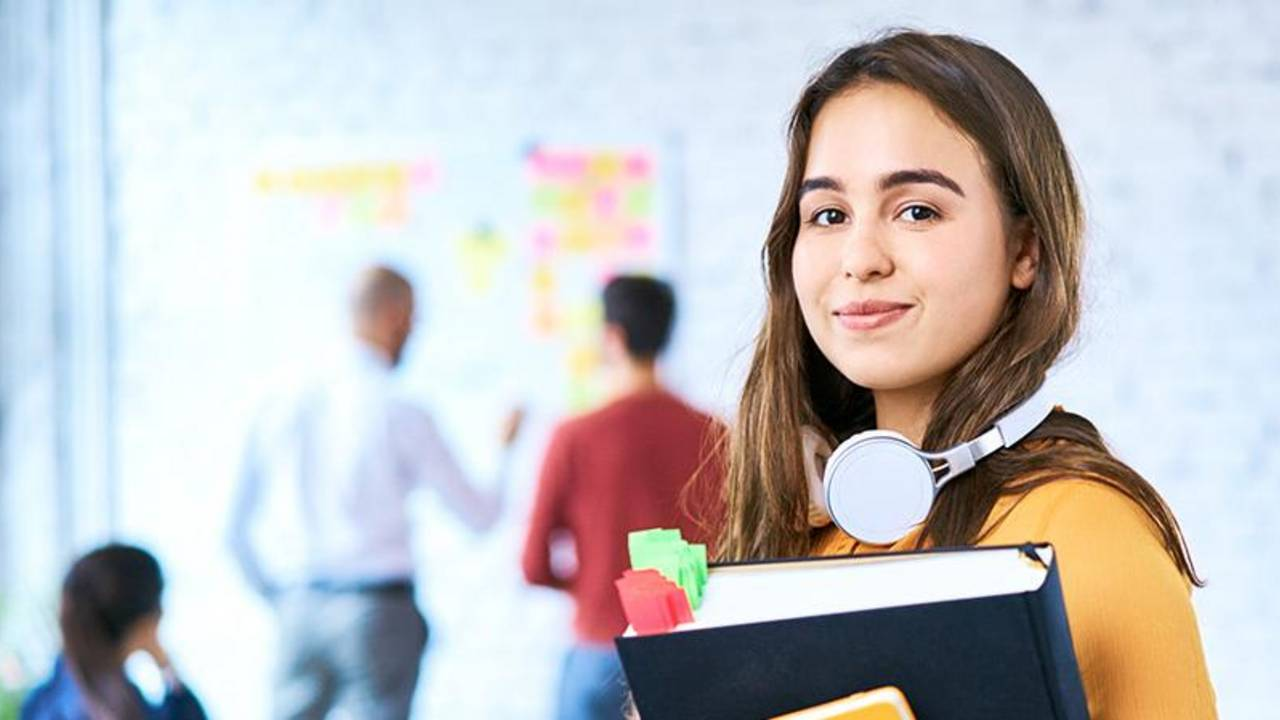 Female student looking into the camera, in the background a bright, modern seminar room