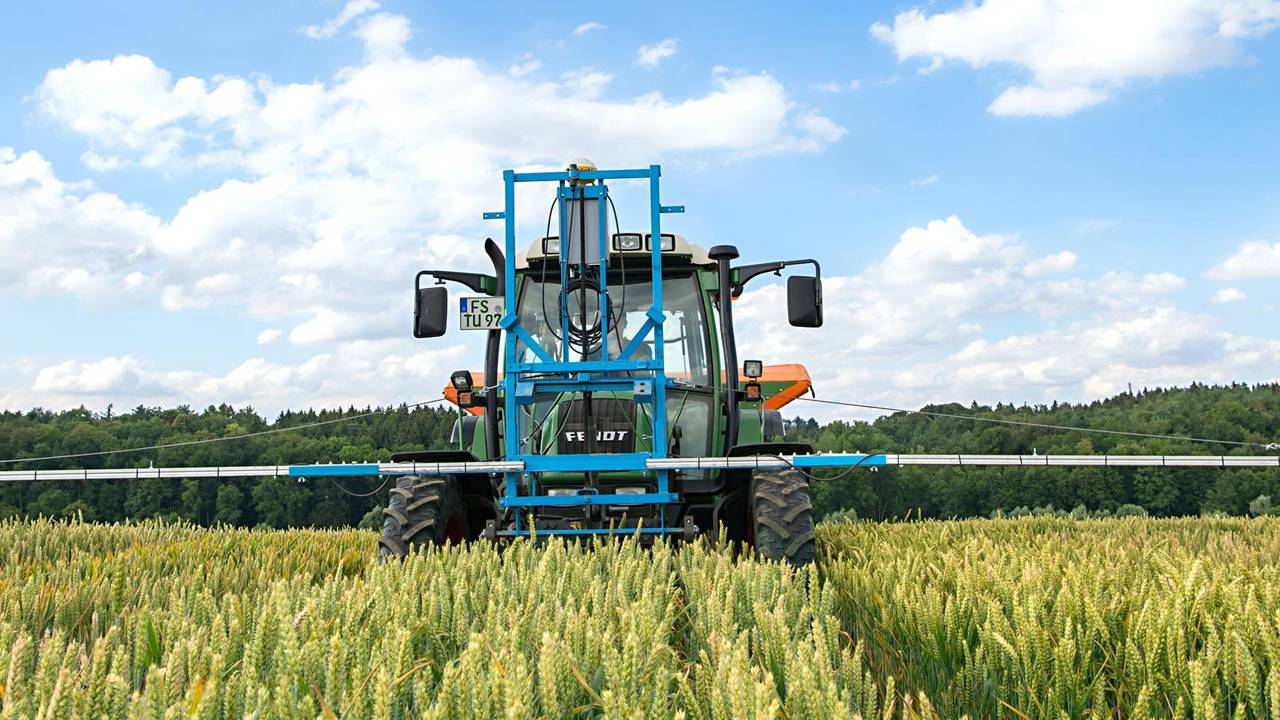 Tractor in grain field with front mounted device with sensors.