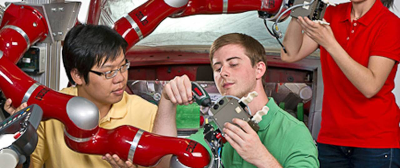 Young researchers working at a robot.