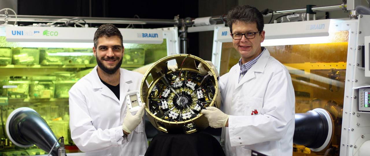 """Prof. Dr. Peter Müller-Buschbaum (left) and Lennart Reb (right) in the laboratories of the Professorship of Functional Materials at the Technical University of Munich with the payload module """"Organic and Hybrid Solar Cells In Space"""" (OHSCIS) in their hands."""