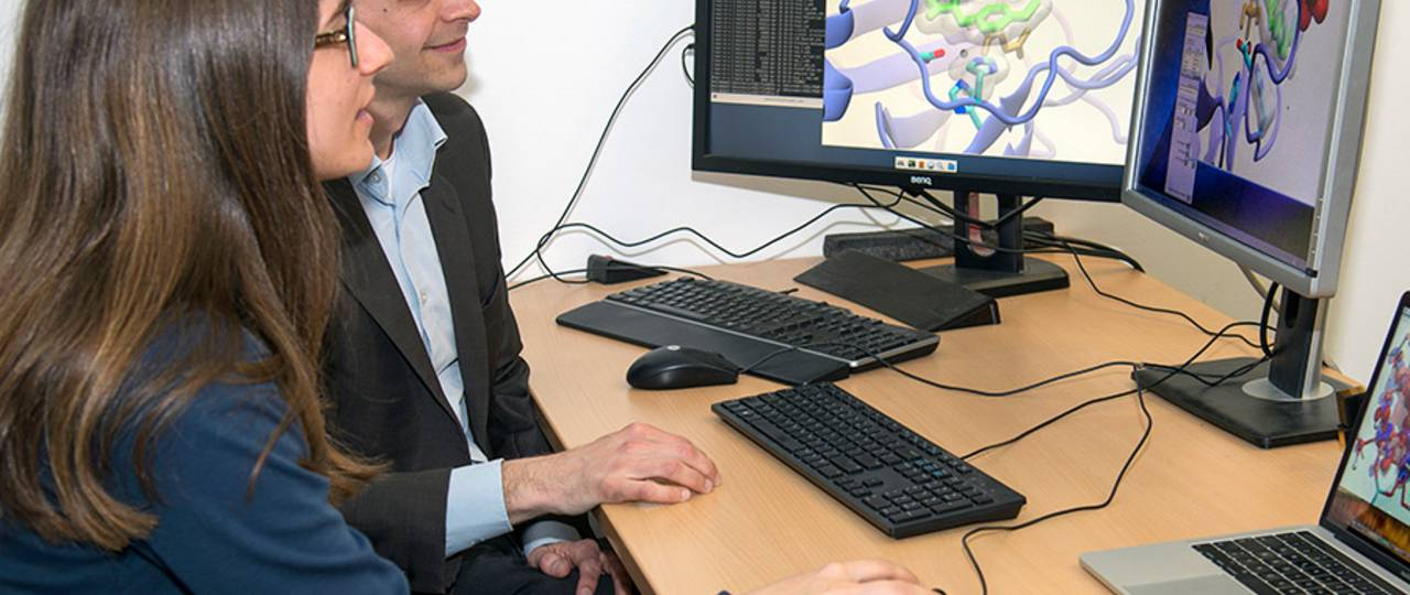 Sophie Mader and Prof. Ville Kaila; on the screens the simulation of the two AsqJ variants. (Image: A. Battenberg / TUM)