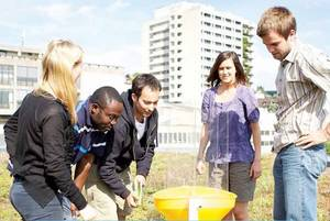 A group of students conducting an experiment in a field.