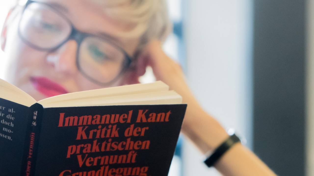 Student reading a book of Immanuel Kant