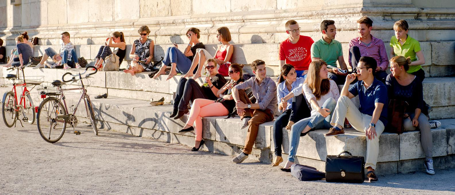 Students of the Technical University of Munich (TUM) are sitting on the steps outside the Glyptothek museum on the Munich Königpslatz square.