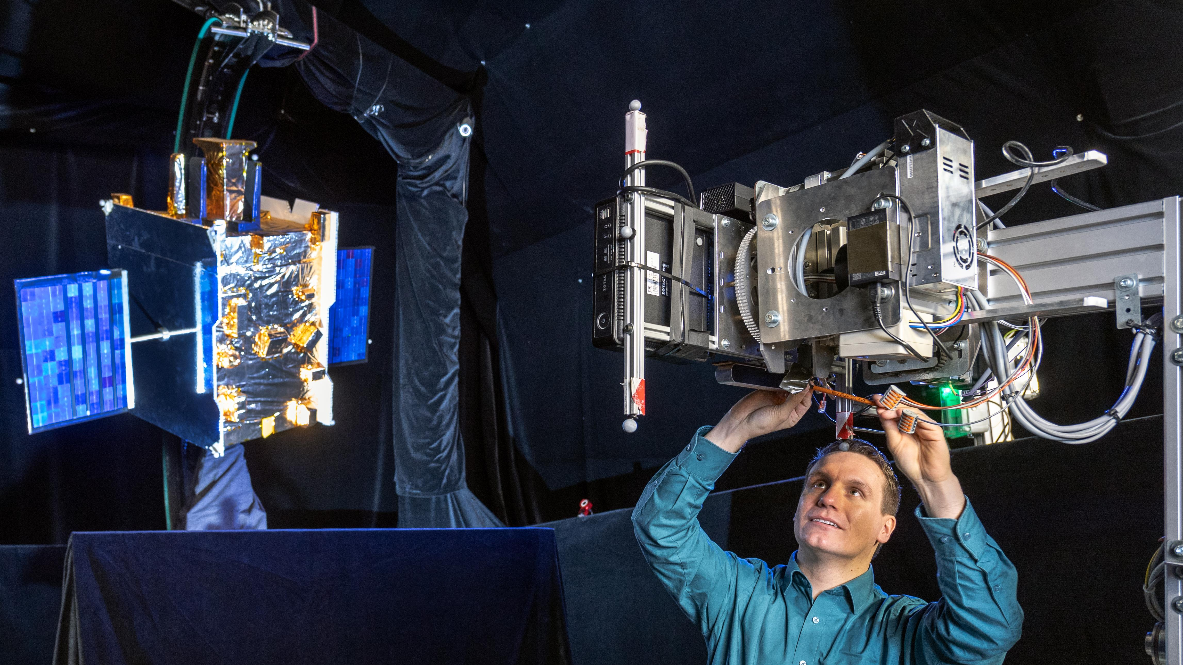 Man is working on a model to simulate satellite maintenance