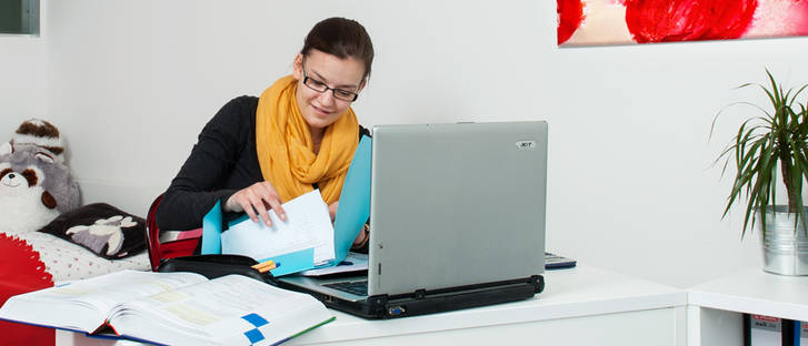 Student in her apartment on a laptop