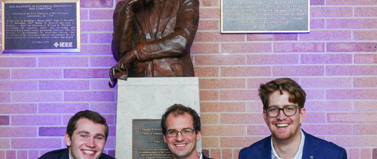 TUM researchers (l-r) Fabian Steiner, Georg Böcherer, and Patrick Schulte with the statue of Claude Shannon, father of information theory. (Image: Denise Panyik-Dale/Alcatel-Lucent)