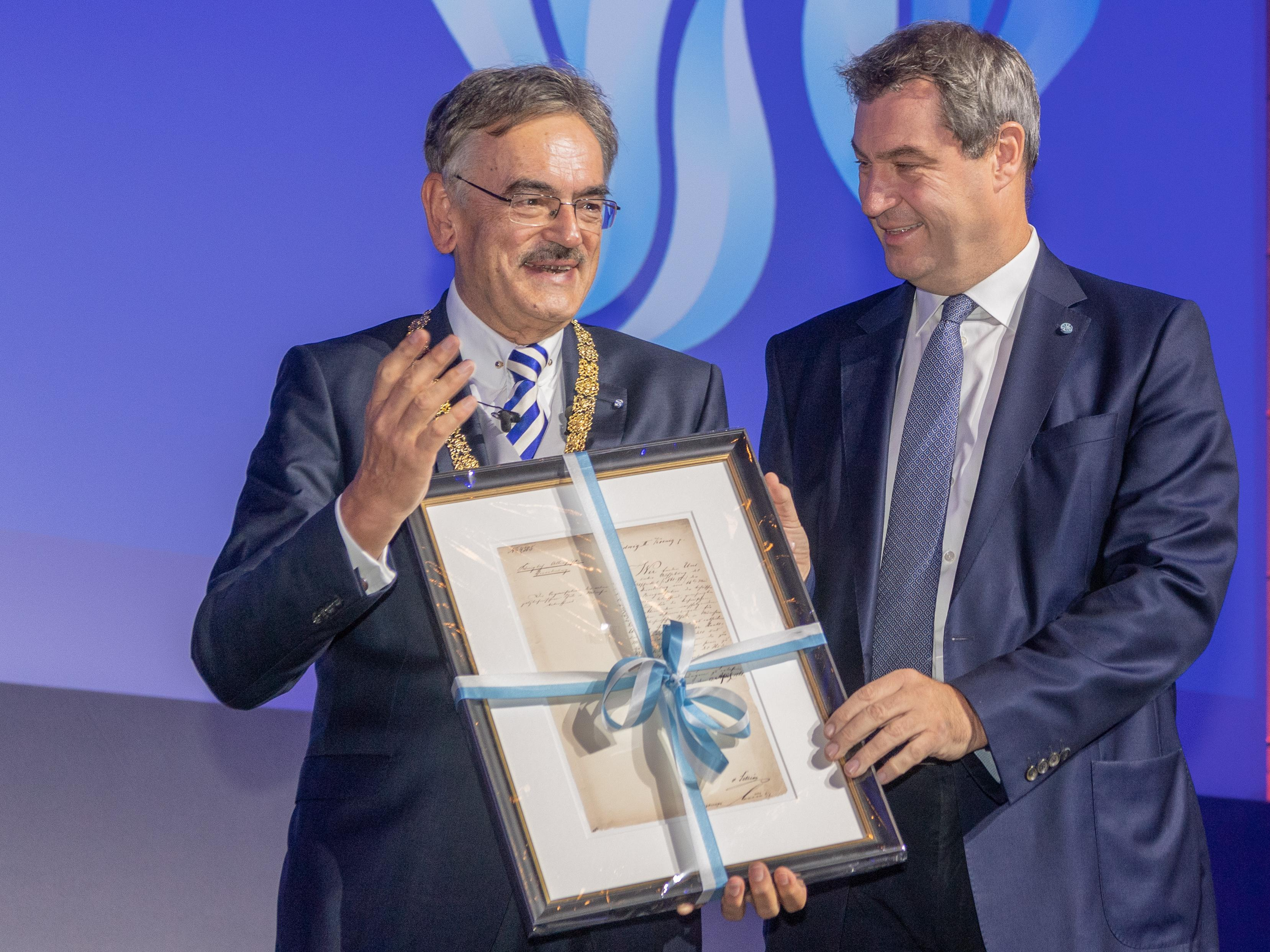 Minister President Markus Söder presents a reproduction of the charter of today's TUM to Wolfgang A. Herrmann.