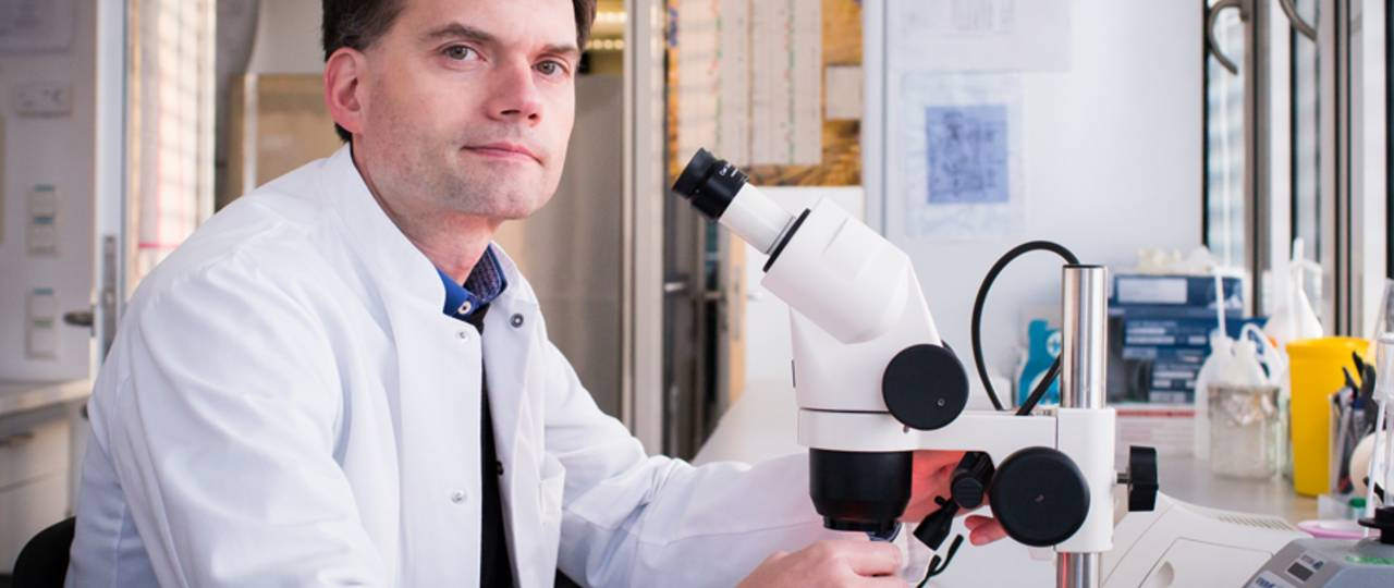 Professor Thomas Korn sitting in front of a microscope .