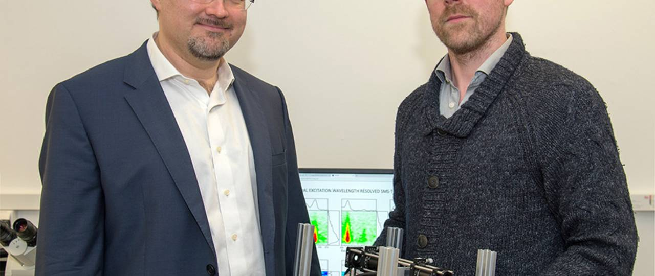 Prof. Dr. Juergen Hauer (left) and first author Erling Thyrhaug with their measuring instrument. In the background, spectra taken with it. (Image: A. Battenberg / TUM)