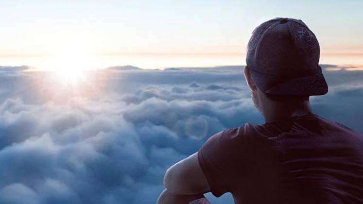 Person sitting on a mountain peak looking over a cloud cover towards the setting sun