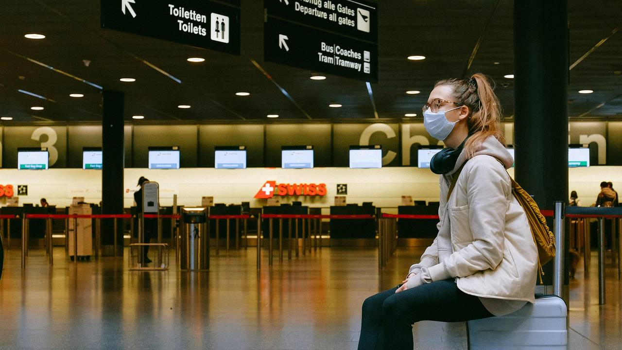 Woman with mouth-nose protection in empty airport terminal