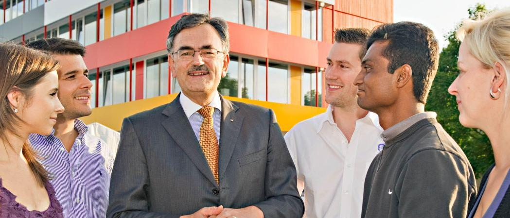 TUM President Prof. Wolfgang A. Herrmann with doctoral candidates in front of the Exzellenzzentrum building in Garching