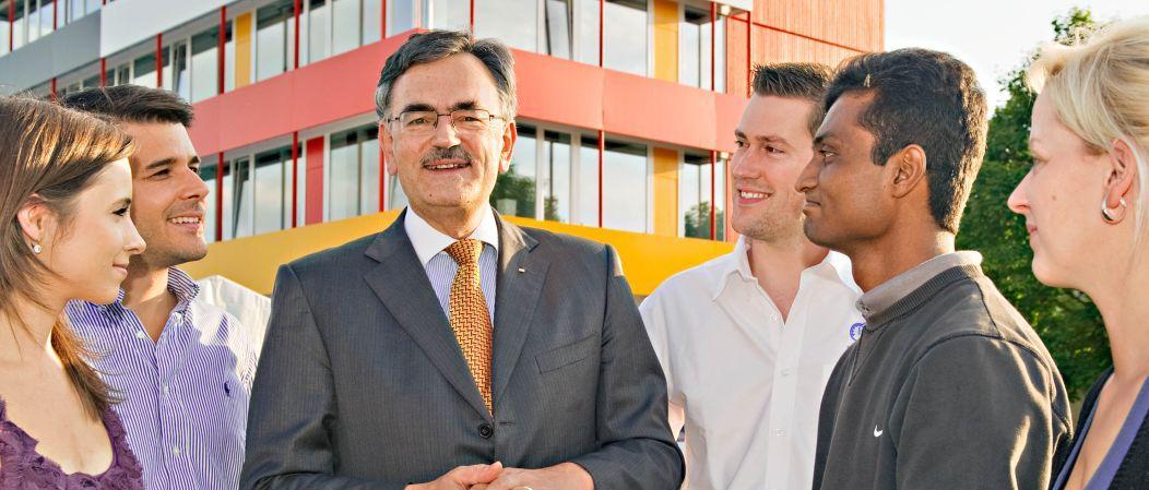 Der Präsident der TUM, Prof. Wolfgang A. Herrmann, mit Doktoranden vor dem Exzellenzzentrum in Garching