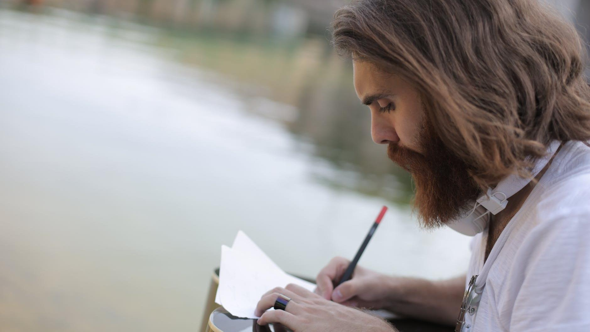 A man writing on a piece of paper
