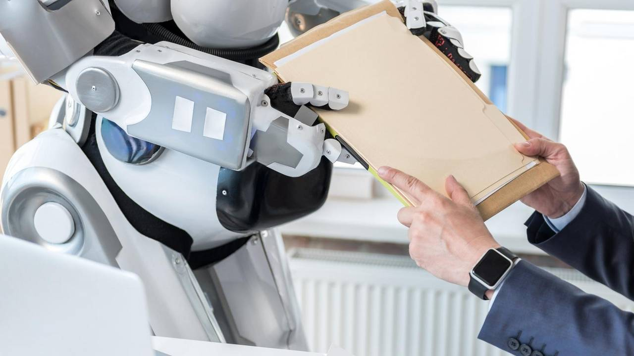 A man hands documents to a robot.