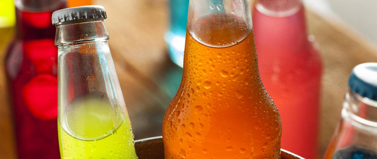 Bottles filled with colorful soft drinks.