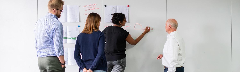 Vier Personen arbeiten an einem Whiteboard