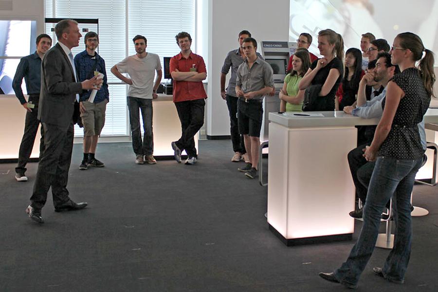 Christian Tropp (links) führt die Stipendiaten durch den Banknotenbereich des Experience Centers (Foto: Giesecke & Devrient)