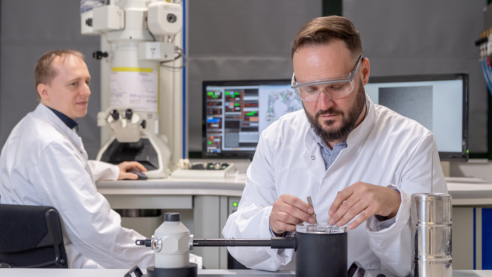 First authors Dr. Christoph Kaiser, transferring a cryo protein preparation into a sample holder cooled with liquid nitrogen and Dr. Carsten Peters at the transmission electron microscope.