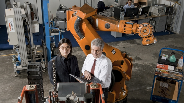 Prof. Thomas Bock and Dr. Seungyel in front of a construction robot