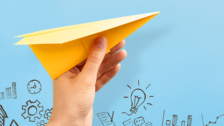 A hand with yellow paper airplane on light blue background with sketches