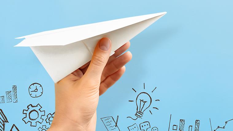 Eine Hand mit weißem Papierflugzeug vor hellblauem Hintergrund mit Skizzen