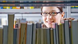 Studentin blickt durchs Bücherregal