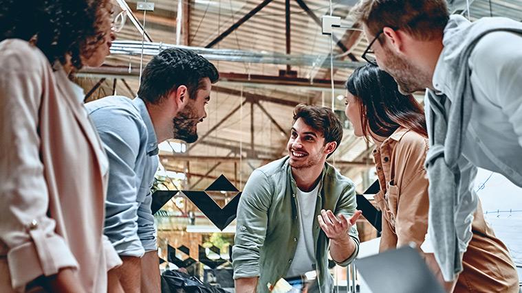 Fünf Studierende stehen an einem Tisch und besprechen ein gemeinsames Projekt