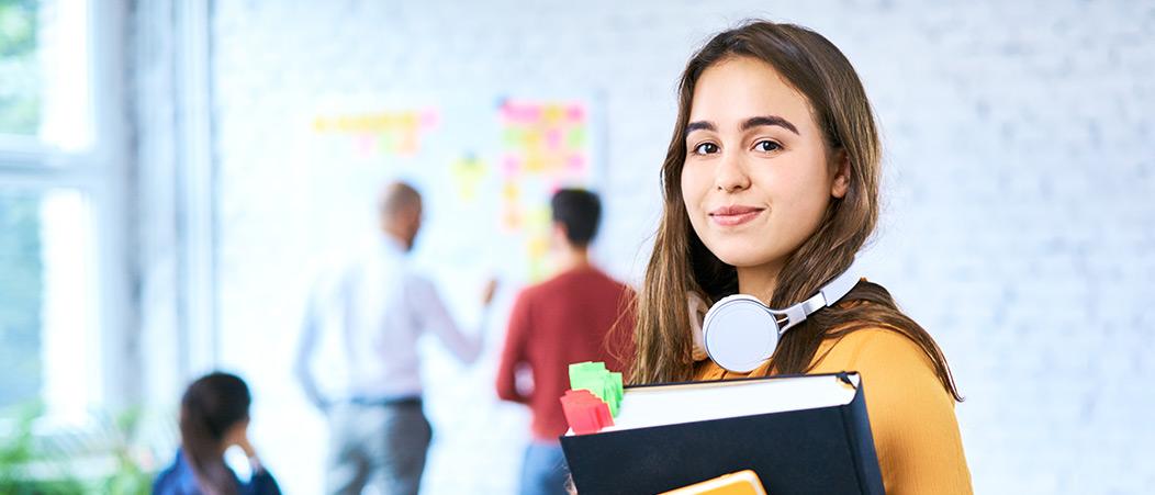 In die Kamera blickende Studentin, im Hintergrund ein heller, moderner Seminarraum