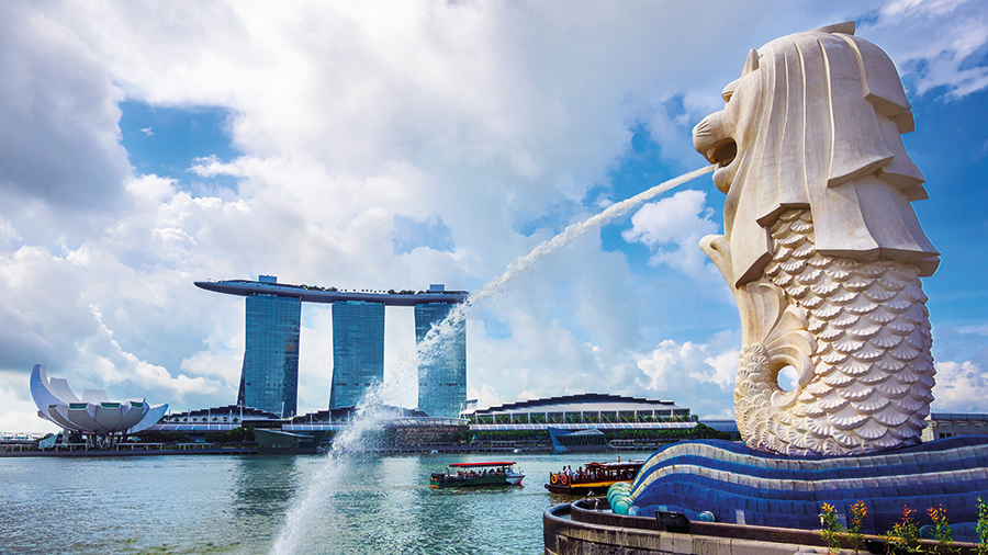 View of Merlion statue, symbol of Singapore, with famous Marina Bay Sands hotel in the background.
