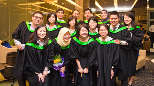 Master graduates in their graduation gown.