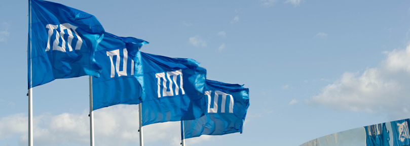 Four blue flags of TUM flying in the wind.