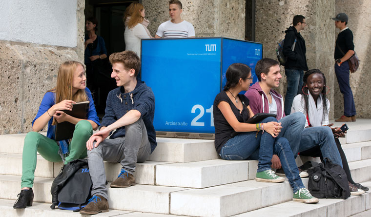 Students are sitting on the stairs in front of the main buildung of the Technical University of Munich on its Munich city campus.