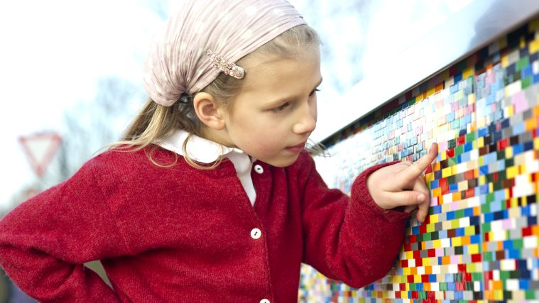 A girl looking at a colorful wall.