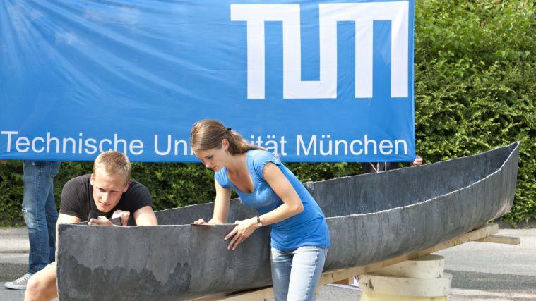 Studierende arbeiten an einem Betonkanu.