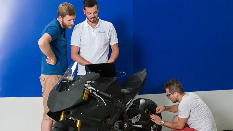 Studierende arbeiten an einem Elektromotorrad.