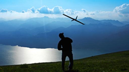 Ein Student lässt sein Modellflugzeug in den Bergen fliegen.