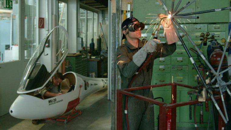 Studierende bauen und schweißen ein Segelflugzeug.