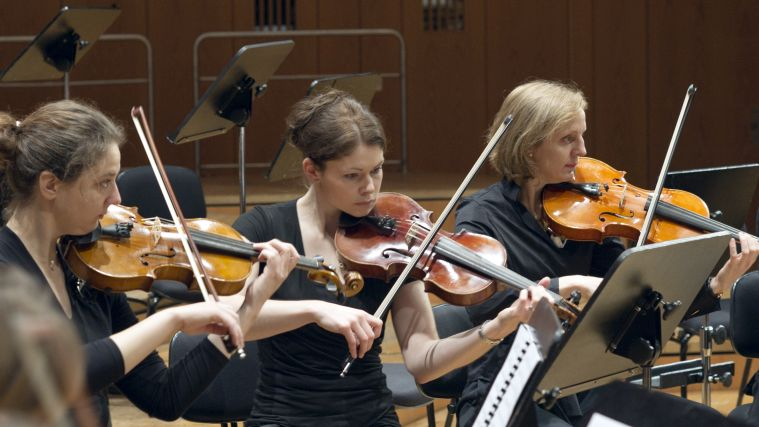 Three violin players of the Symphonic Ensemble during a concert.