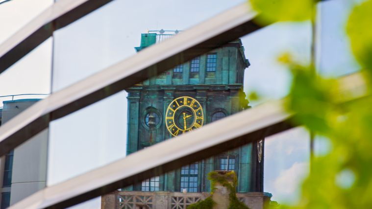 TUM's clocktower is reflected by a glass pane.